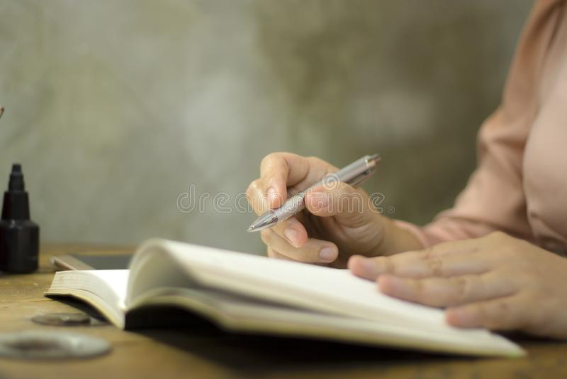 Giovane donna di affari che lavora con una penna all'ufficio, lei che resta fuori orario fotografia stock libera da diritti