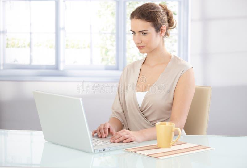Giovane donna di affari che lavora nell'ufficio luminoso fotografia stock libera da diritti
