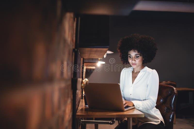 Giovane donna di affari che lavora tardi sul computer portatile in ufficio immagine stock libera da diritti