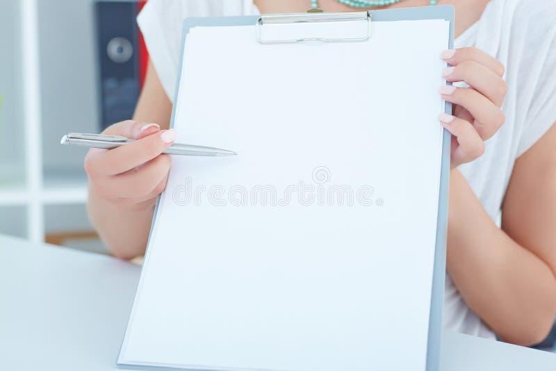 Giovane donna di affari che mostra lavagna per appunti con carta in bianco Consegna appena la tavola fotografie stock
