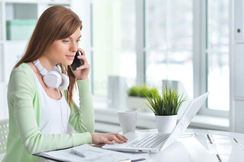 Giovane donna di affari che parla sul telefono mentre sedendosi nell'ufficio fotografia stock
