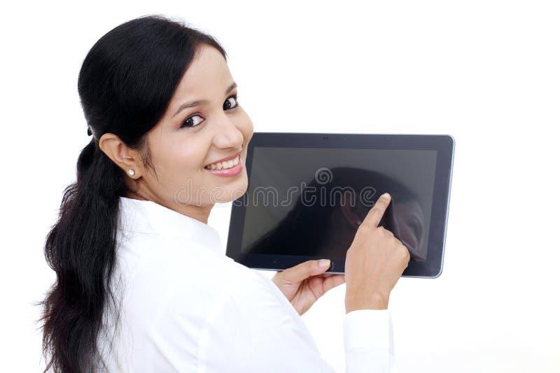 Giovane donna di affari che per mezzo del computer digitale della compressa fotografia stock