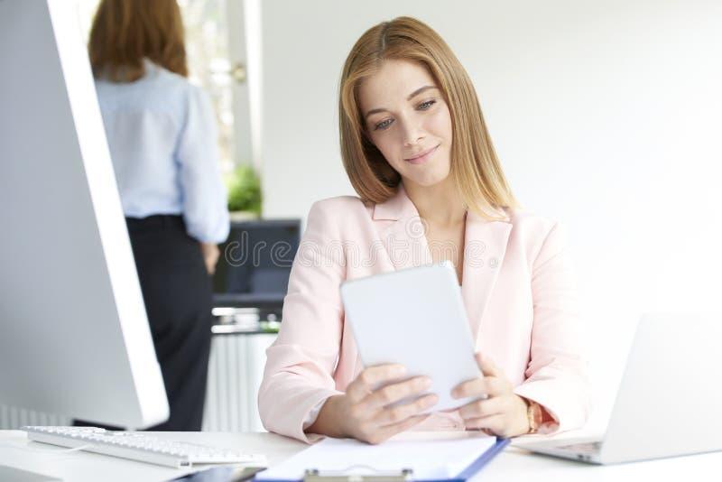 Giovane donna di affari che per mezzo della compressa digitale immagini stock libere da diritti
