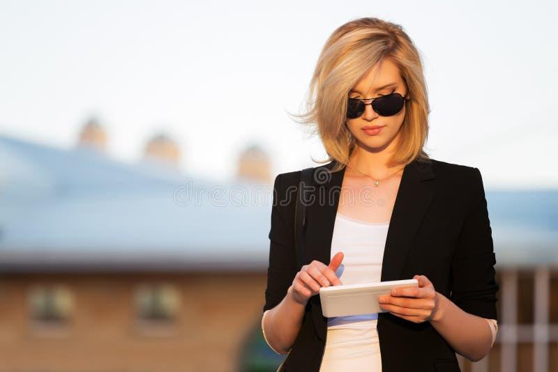 Giovane donna di affari che per mezzo di un calcolatore del ridurre in pani immagine stock