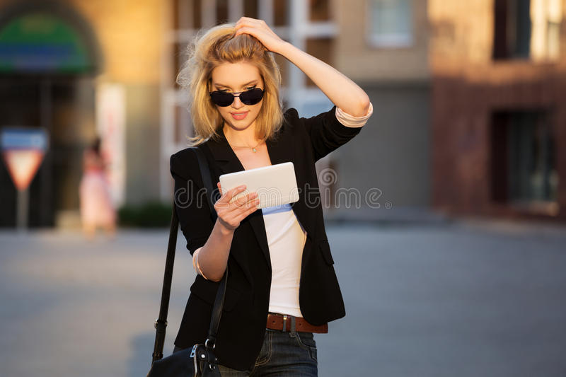 Giovane donna di affari che per mezzo di un computer digitale della compressa fotografie stock libere da diritti