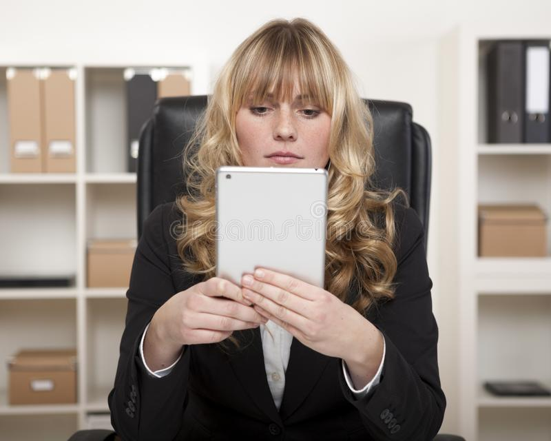 Giovane donna di affari che per mezzo di una compressa sul lavoro fotografie stock