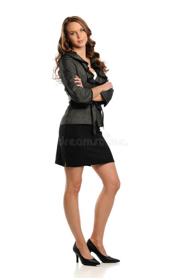 Giovane donna di affari che si leva in piedi con le sue braccia attraversate immagini stock