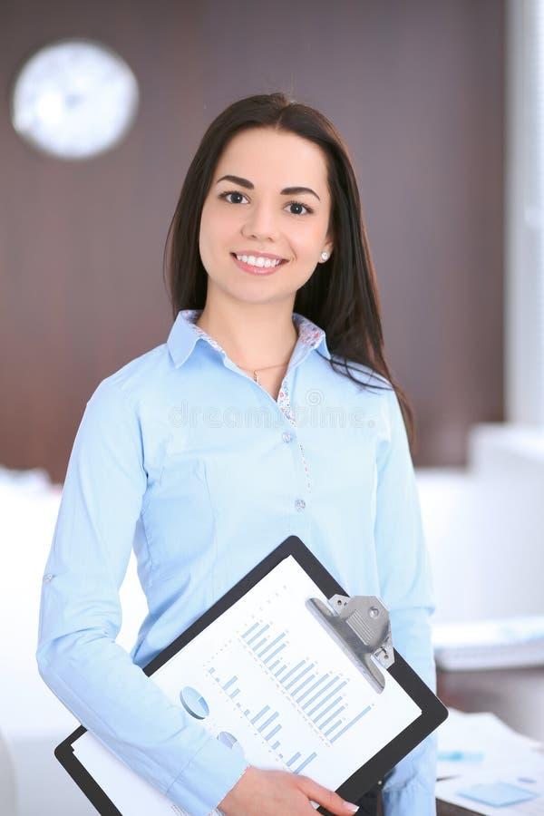 Giovane donna di affari che si leva in piedi nell'ufficio fotografie stock libere da diritti