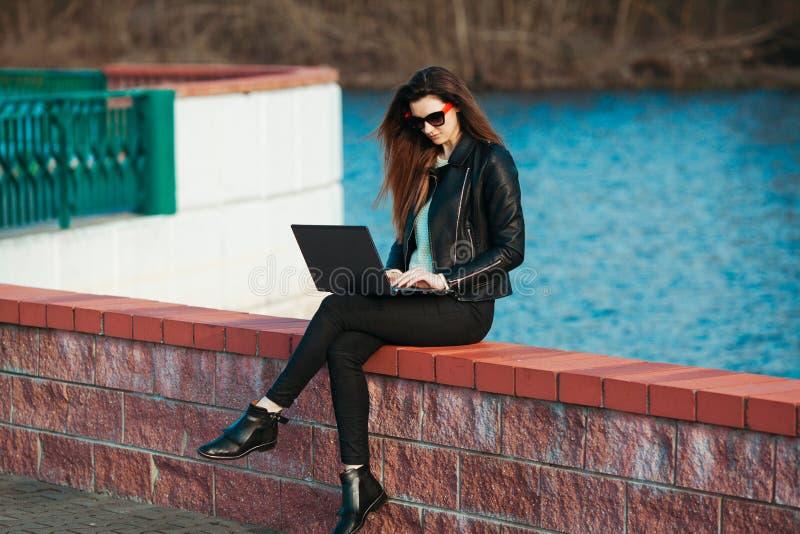 Giovane donna di affari che si siede ad un computer portatile fotografie stock