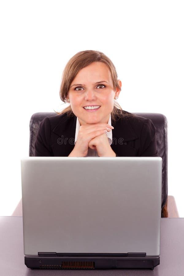 Giovane donna di affari che si siede alla scrivania con il computer portatile e il looki immagini stock libere da diritti