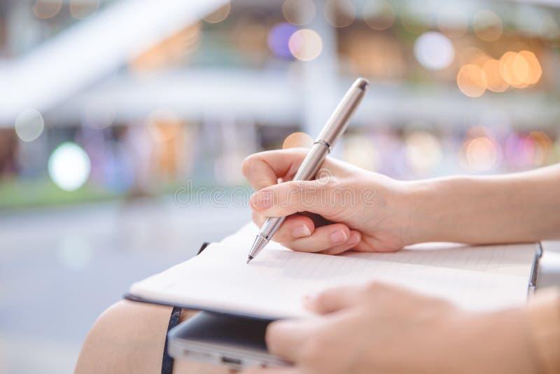 Giovane donna di affari che si siede alla tavola in caffè e che scrive dentro non fotografia stock