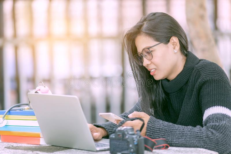 Giovane donna di affari che si siede alla tavola e che per mezzo dello smartphone Sullo scrittorio è il computer della compressa fotografia stock