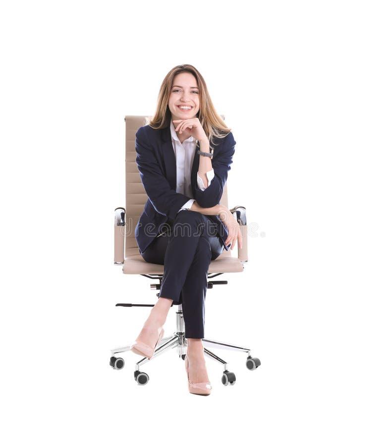 Giovane donna di affari che si siede nella sedia dell'ufficio fotografia stock