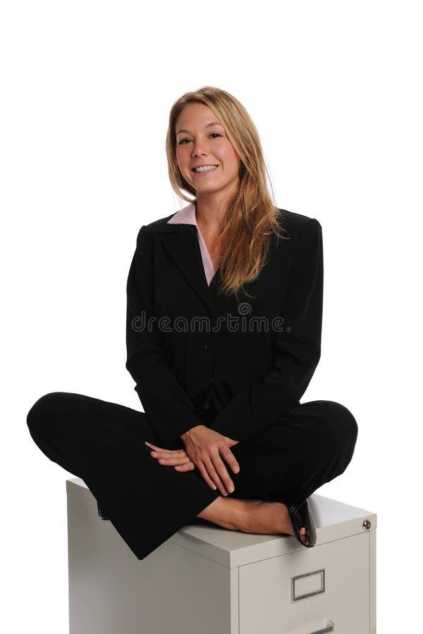Giovane donna di affari che si siede su un armadietto fotografia stock libera da diritti