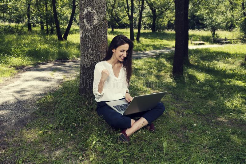 Giovane donna di affari che si siede su una terra e che lavora al suo computer portatile e che fa gesto del successo in un parco  fotografie stock