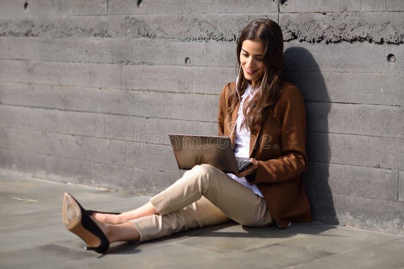 Giovane donna di affari che si siede sul pavimento che esamina il suo compu del computer portatile fotografia stock libera da diritti