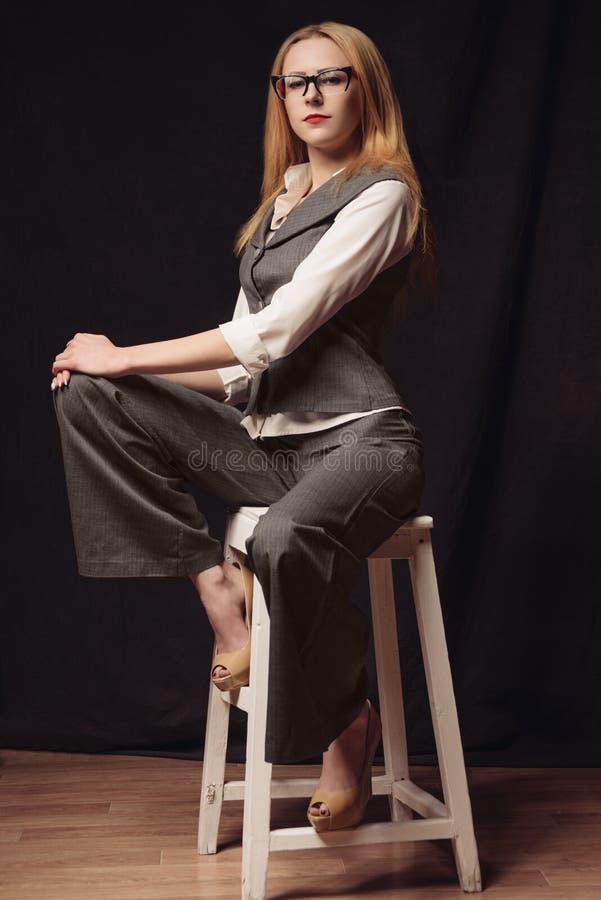 Giovane donna di affari che si siede sulla sedia sopra fondo scuro fotografia stock