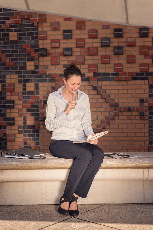 Giovane donna di affari che si siede in un atrio immagine stock libera da diritti