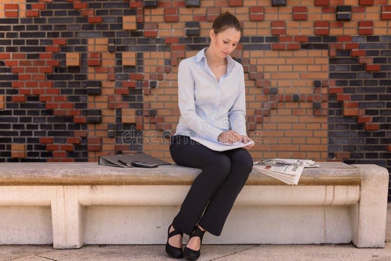 Giovane donna di affari che si siede in un atrio fotografia stock libera da diritti