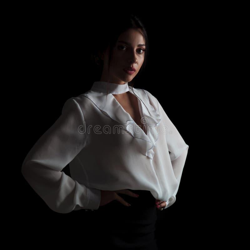 Giovane donna di affari che sta con le mani sulla vita fotografia stock
