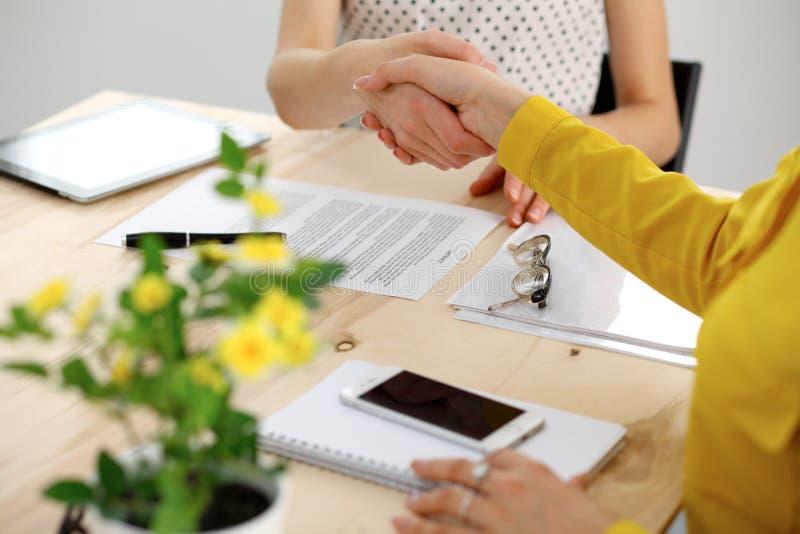 Giovane donna di affari che stringe le mani dopo la firma del contratto fotografia stock