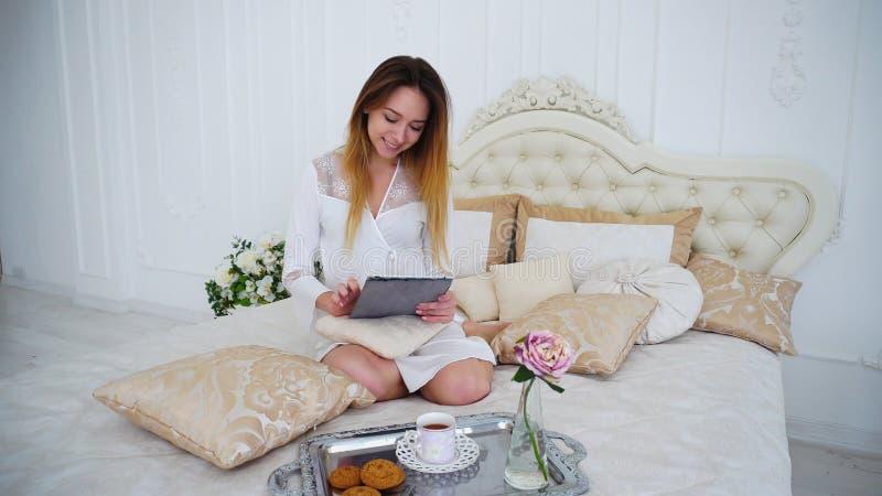Giovane donna di affari che usando compressa per lavorare online e la sorsata delle bevande della bevanda fotografie stock