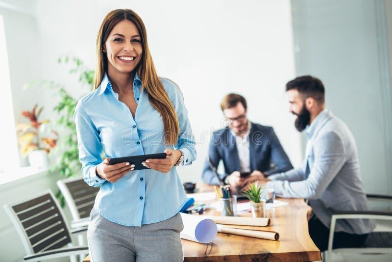 Giovane donna di affari che utilizza compressa digitale mentre collega nel fondo immagini stock libere da diritti