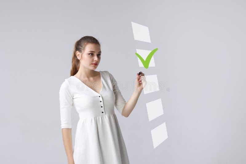 Giovane donna di affari che verifica la scatola della lista di controllo Fondo grigio fotografia stock