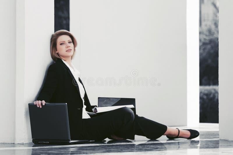 Giovane donna di affari con il computer portatile che si siede alla parete fotografie stock libere da diritti
