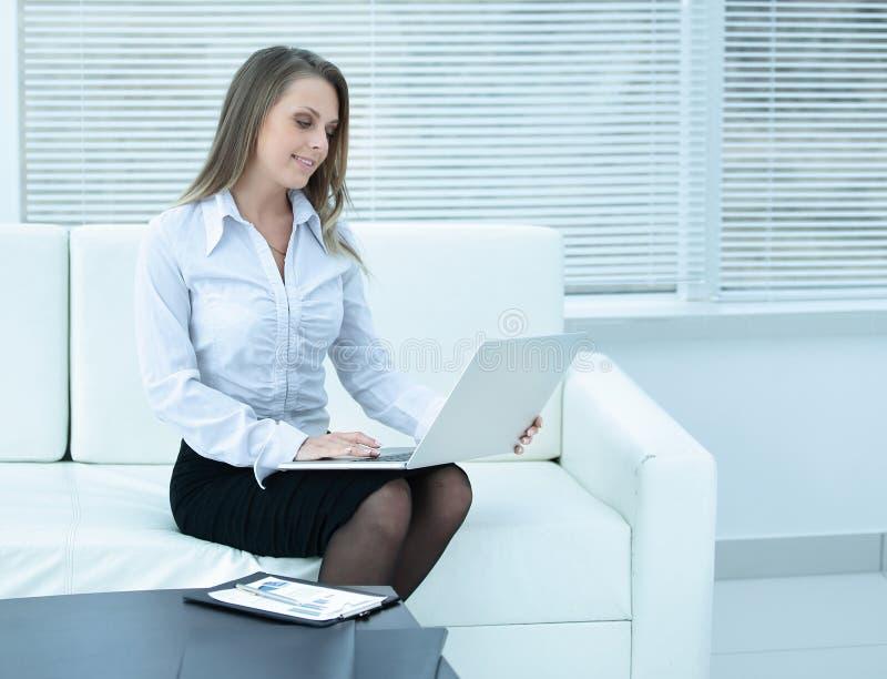 Giovane donna di affari con il computer portatile sui precedenti dell'ufficio fotografia stock
