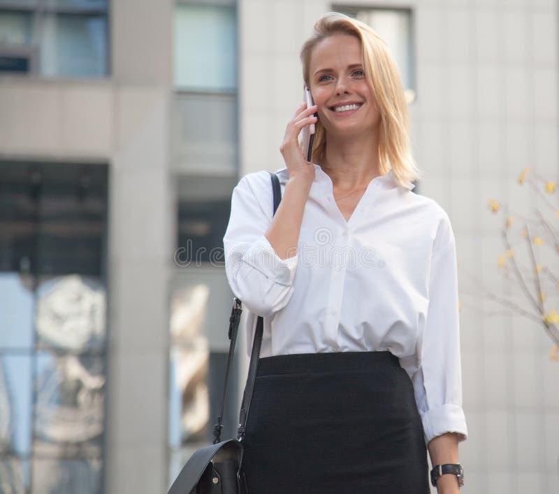 Giovane donna di affari davanti all'edificio per uffici facendo uso del suo telefono cellulare immagini stock libere da diritti