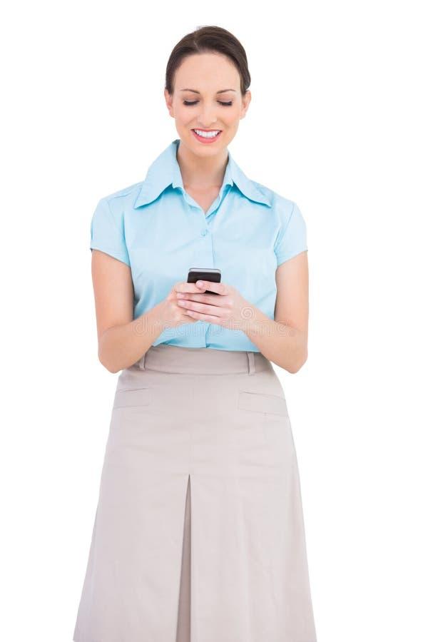 Giovane donna di affari di classe allegra che invia messaggio di testo fotografia stock