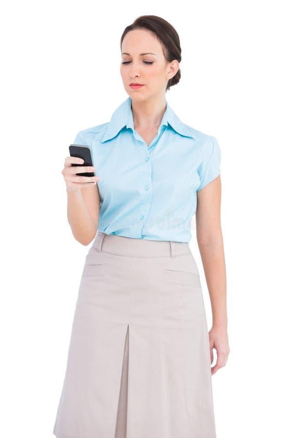 Giovane donna di affari di classe seria che invia messaggio di testo immagine stock
