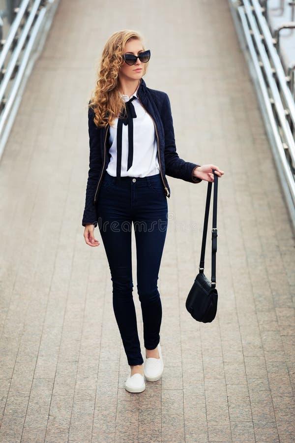 Giovane donna di affari di modo in occhiali da sole sulla via della città fotografia stock libera da diritti