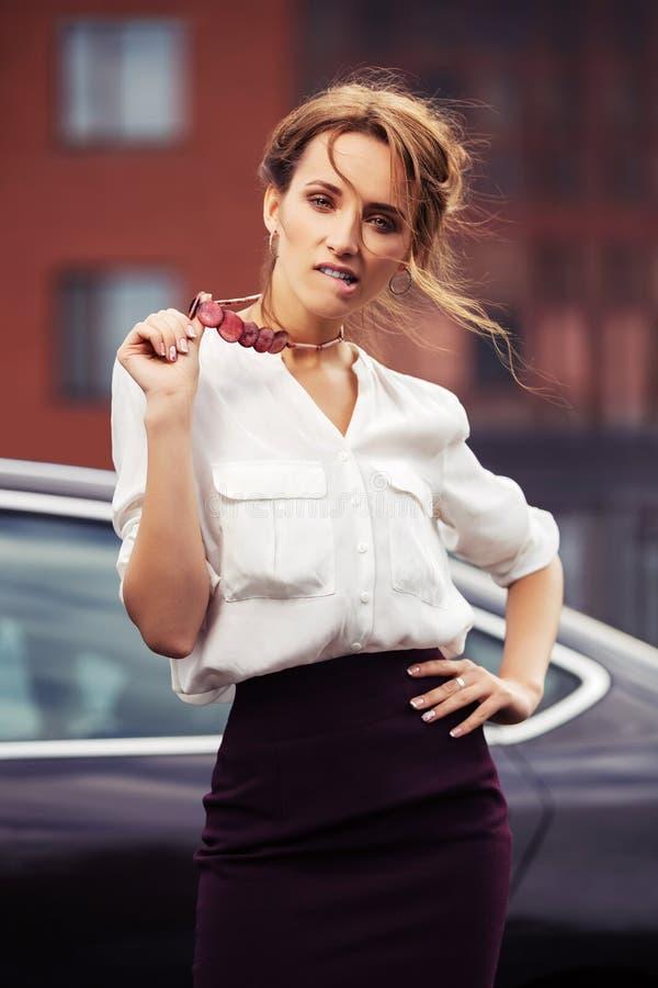 Giovane donna di affari di modo sulla via della città accanto alla sua automobile immagini stock