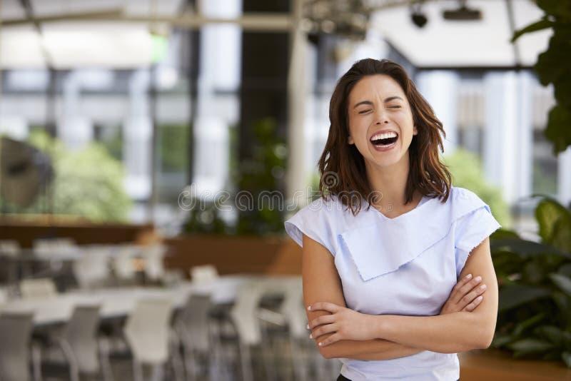 Giovane donna di affari di risata della corsa mista con le armi attraversate immagini stock libere da diritti