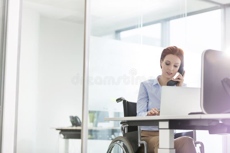 Giovane donna di affari disabile sicura che lavora allo scrittorio in ufficio fotografie stock libere da diritti
