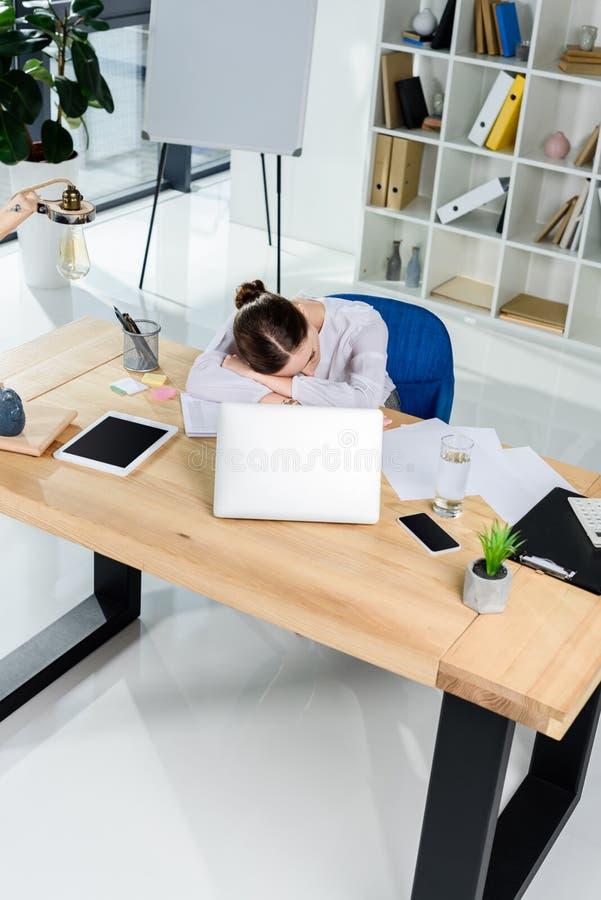 Giovane donna di affari esaurita che dorme al suo scrittorio all'ufficio davanti a immagini stock libere da diritti