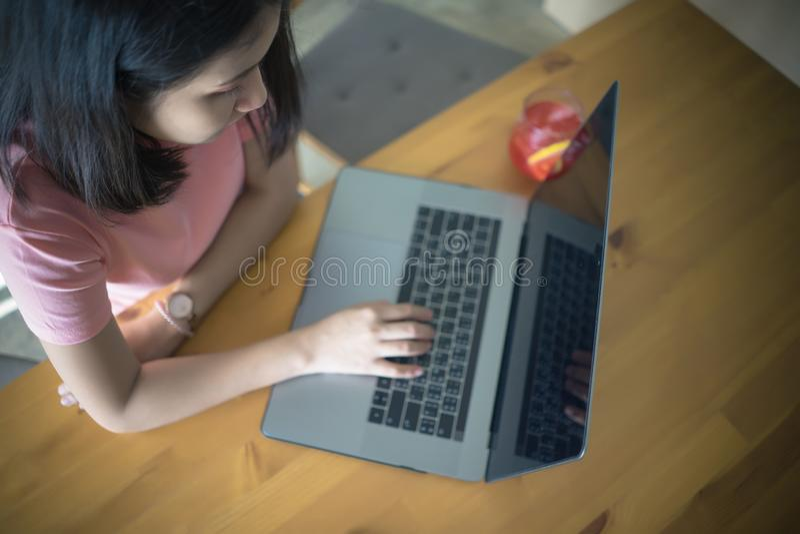 Giovane donna di affari facendo uso di funzionamento del computer portatile sulla tavola di legno con lo spazio della copia Ragaz immagine stock libera da diritti