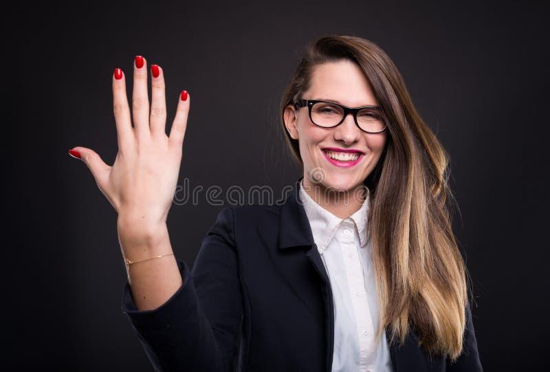 Giovane donna di affari felice che conta cinque dita immagini stock libere da diritti