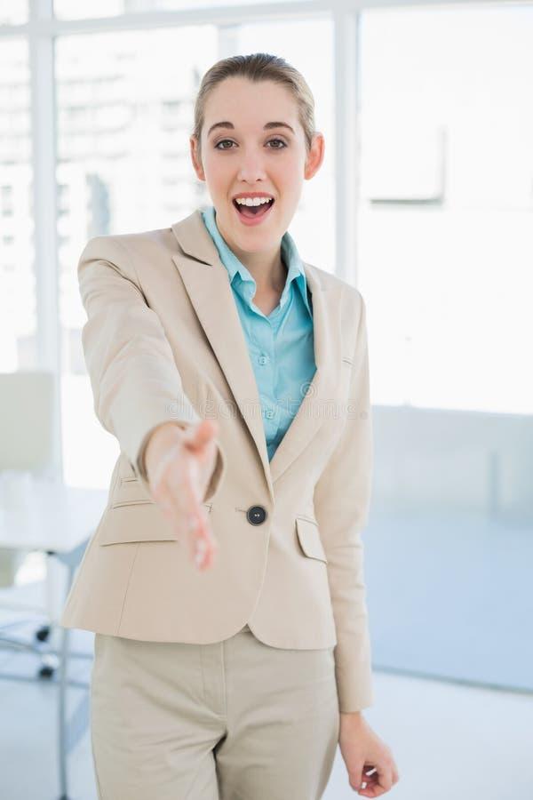 Giovane donna di affari felice che raggiunge la sua mano amichevole fotografie stock