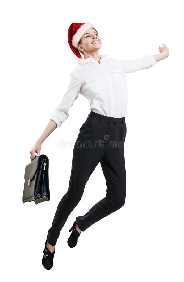 Giovane donna di affari felice nel salto del cappello di natale fotografia stock libera da diritti