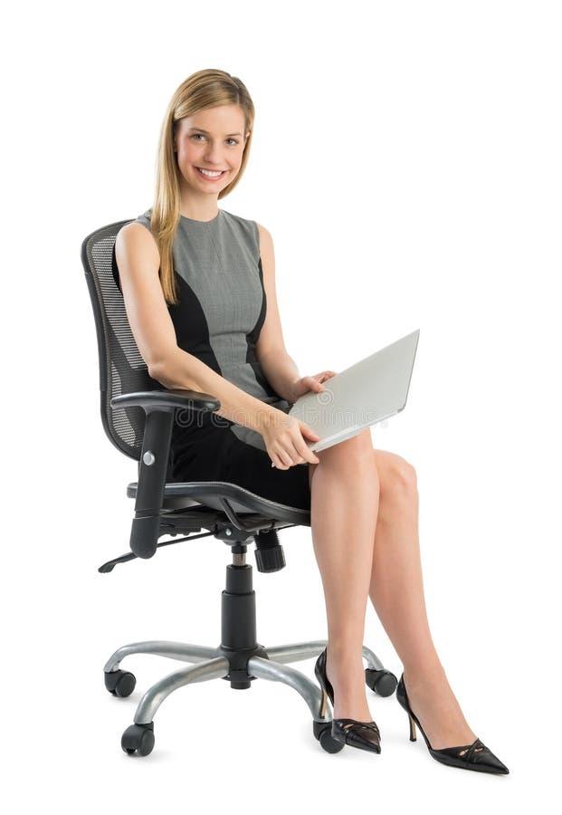 Giovane donna di affari With File Sitting sulla sedia dell'ufficio fotografia stock