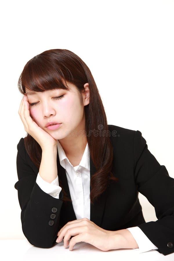 Giovane donna di affari giapponese che dorme sullo scrittorio immagini stock libere da diritti