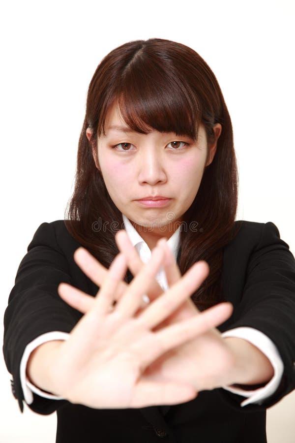 Giovane donna di affari giapponese che fa gesto di arresto immagini stock
