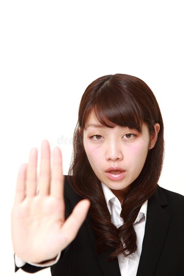 Giovane donna di affari giapponese che fa gesto di arresto fotografia stock libera da diritti