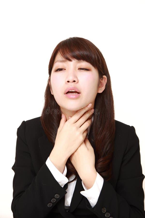 Giovane donna di affari giapponese che ha dolore della gola fotografie stock