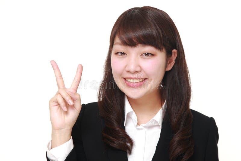 Giovane donna di affari giapponese che mostra un segno di vittoria fotografie stock