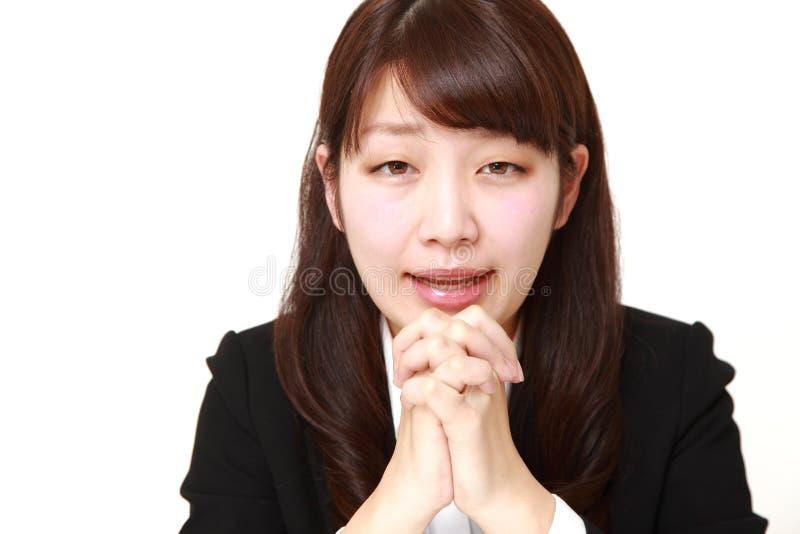 giovane donna di affari giapponese che piega le sue mani nella preghiera immagini stock libere da diritti