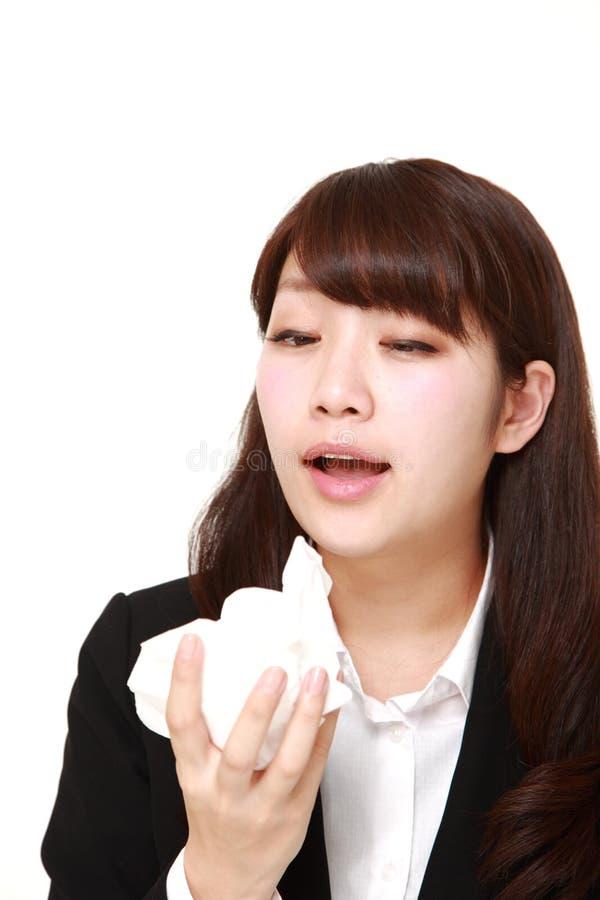 giovane donna di affari giapponese con un'allergia che starnutisce nel tessuto immagine stock